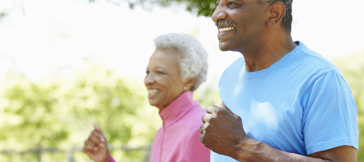 Senior African American Couple Jogging Together In Park And Smiling